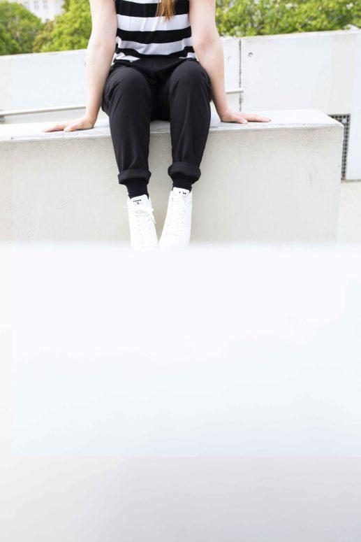 Swantje sitzt auf einer Mauer und man sieht ihre Sneaker Hose