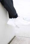 Die Beine baumeln über einer Mauer und man sieht den hochgekrempelten Hosensaum und die Sneaker im Detail