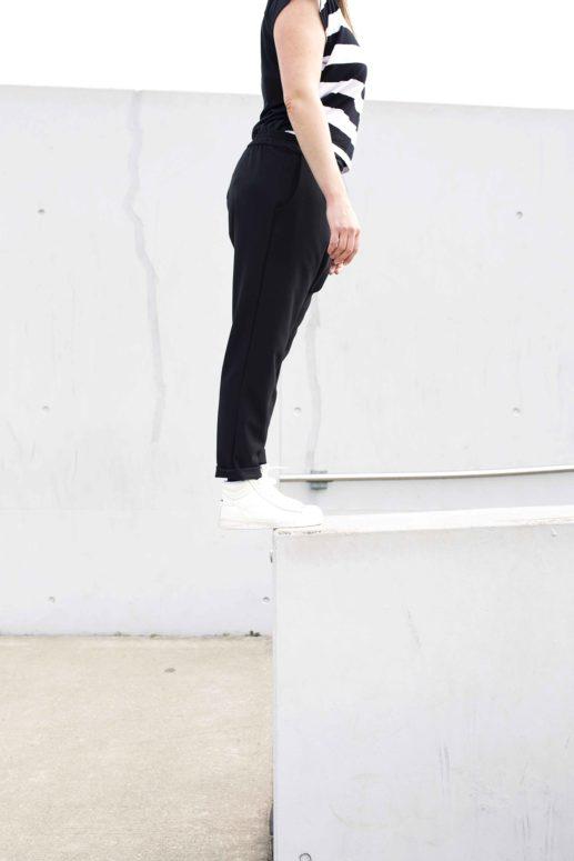 Swantje steht an der Kante einer Mauer und man sieht ihre Sneaker Hose von der Seite
