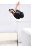 Swantje steht in der Hocke auf der Kante einer Mauer und ist bereit zu springen