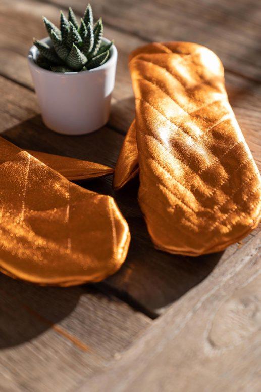 Orangefarbene Lederhandschuhe liegen auf einem Tisch