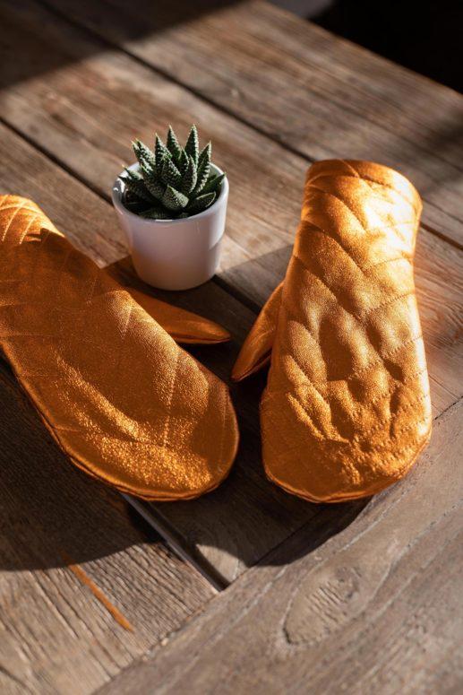 orangefarbene Lederhandschuhe strahlen im Sonnenschein