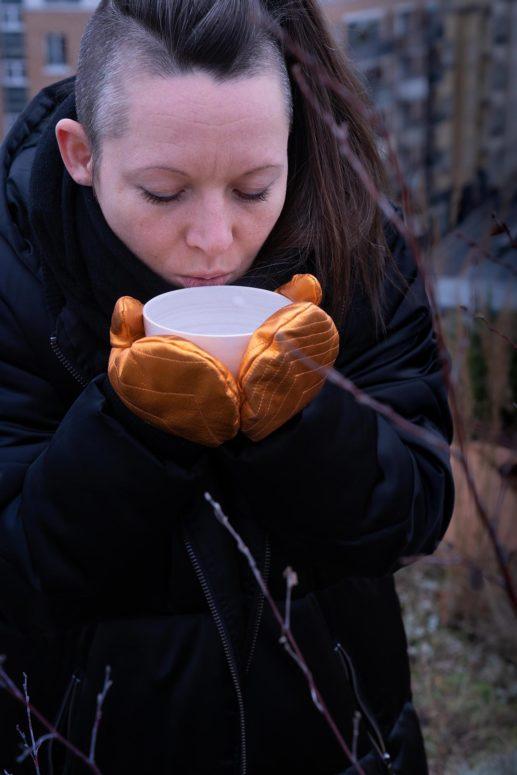 Swantje trinkt aus einer Tasse Tee und trägt Fäustlinge