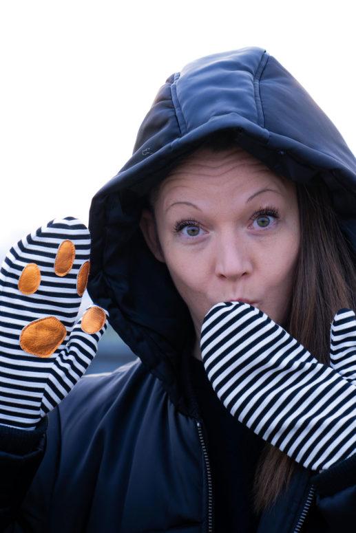 Swantje trägt Fäustlinge aus Sweatstoff und hält eine Hand vor den Mund