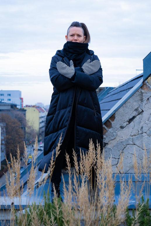 Swantje steht auf einem Dachsims und verschränkt ihre Hände mit gestreiften Fäustlingen