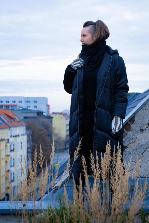 Swantje steht hoch oben auf einem Dach und hält mit einer Hand ihre Jacke zu