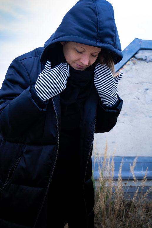 Swantje hält ihre Jacke mit zwei gestreiften Jerseyfäustlingen fest